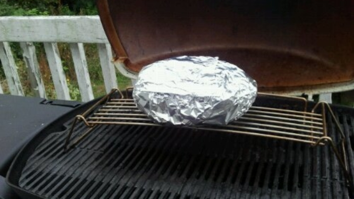 Roast beef in tinfoil on a barbecue