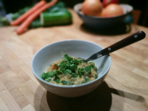 A photo of a bowl of lentil and vegetable stew, garnished with cilantro.